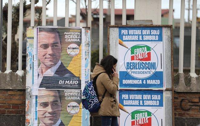 Una mujer delante de carteles electorales en Italia