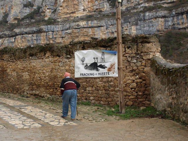 Hombre camina junto a cartel contra el fracking
