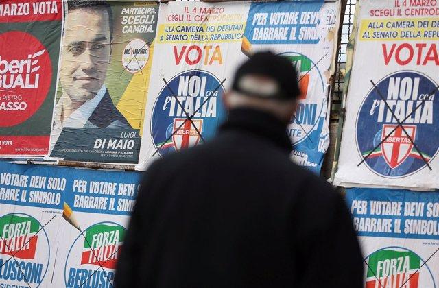 Un hombre delante de carteles electorales en Italia