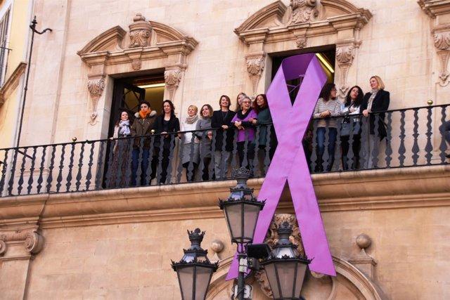 Cort cuelga lazo morado apoyo al Día Internacional de la Mujer