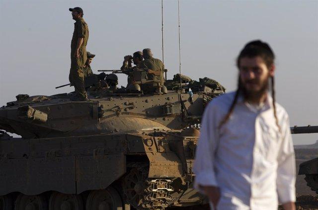 Un ultraortodoxo o haredi junto a un carro de combate israelí