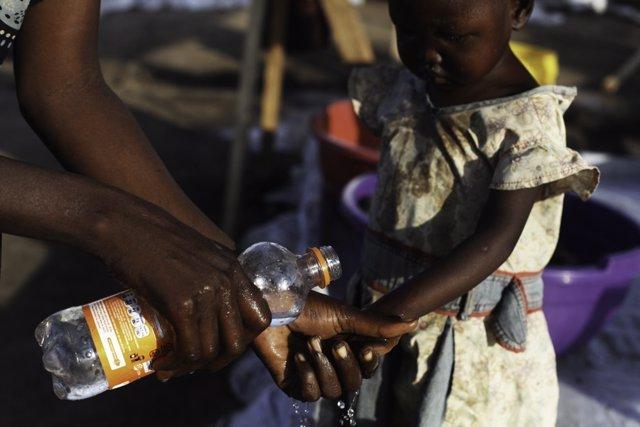 Una madre lava las manos a su hija para evitar el cólera en Sudán del Sur