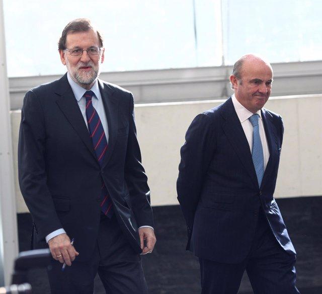 Luis de Guindos y Rajoy a su llegada a una jornada de la Cámara de Comercio