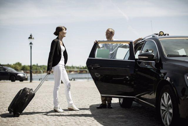 Mujer con maleta en coche de alquiler