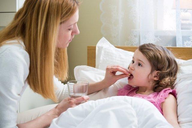 Pastilla, niña enferma, aspirina