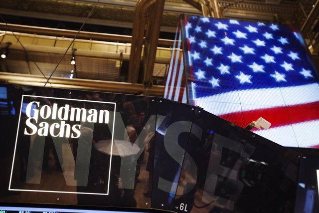 The Goldman Sachs logo is displayed on a post above the floor of the New York St