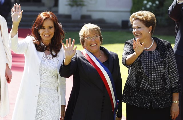 Chile's new President Michelle Bachelet (C) wave to the media with Argentina's P