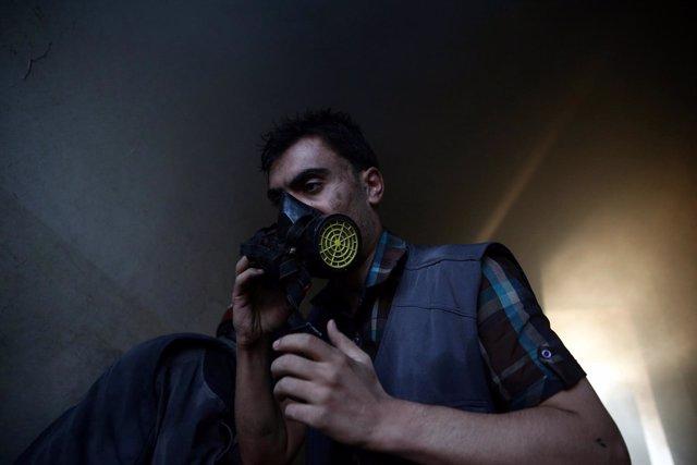 Un miembro de la defensa civil respira a través de una máscara