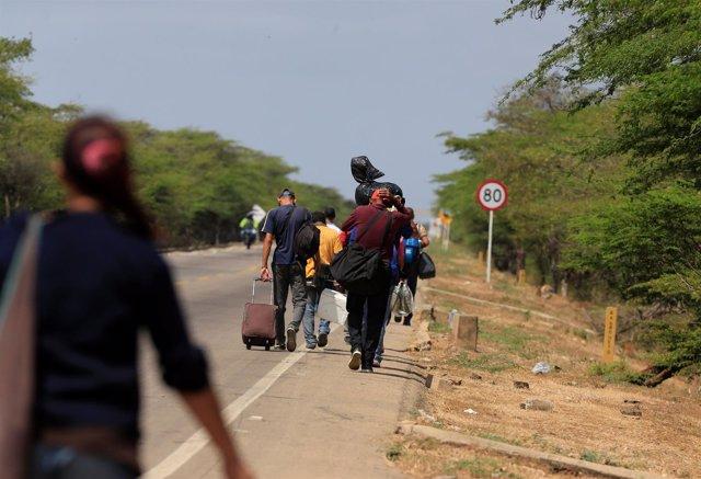 Inmigrantes venezolanos caminan tras entrar en Colombia