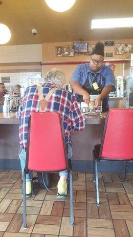 Camarera Evoni Williams le corta la comida a un anciano que no puede hacerlo