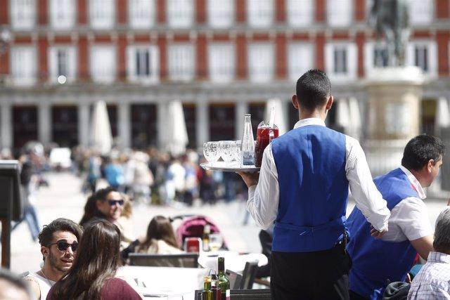 Camarero sirviendo a una mesa. Foto de archivo.