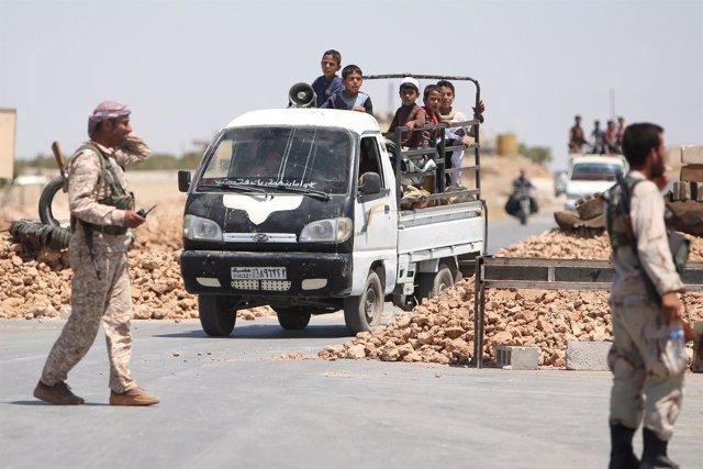 Rebeldes sirios ante una camioneta con niños en Manbij