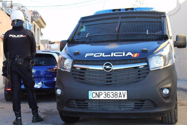 Un agente de Policía Nacional junto a su vehículo