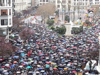El humo y la pólvora de la 'mascletà' de la Pirotecnia Turís sobrevuelan los paraguas en este lluvioso sábado