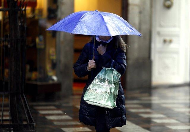 Una mujer sostiene un paraguas bajo la lluvia