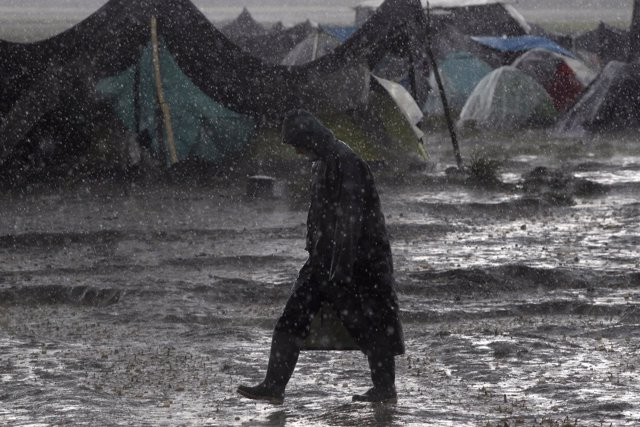 A refugee walks under heavy rainfall at a makeshift camp for migrants and refuge
