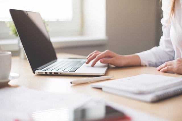 Foto de recurso de una mujer trabajando con un ordenador portátil