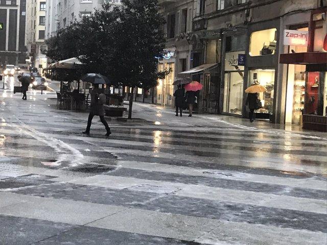 Jornada de lluvia y granizo en Santander, gente con paraguas, lluvia, frío