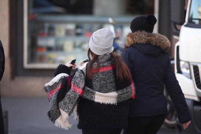Jóvenes caminan por la calle un día de invierno