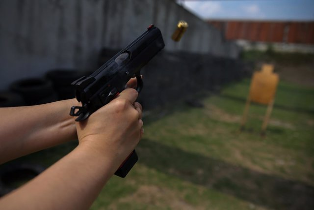 A woman shoots at target during a practice session at a shooting range in Bangko