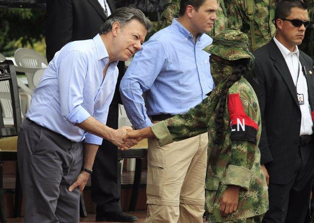 El presidente de Colombia, Juan M. Santos, y un miembro del ELN