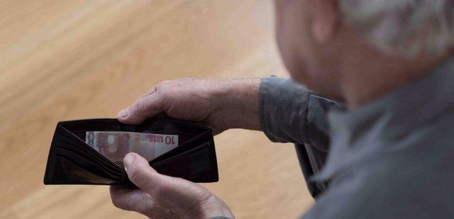 Un pensionista mira su cartera