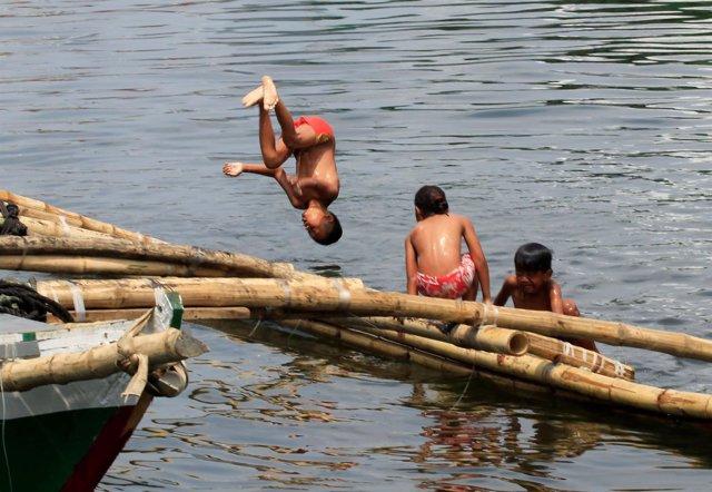 Foto de archivo de niños jugando en la Bahía de Manila.