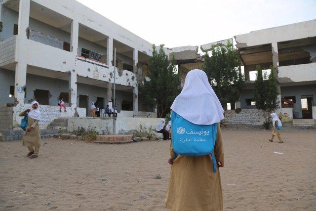 Una niña entra en el patio de una escuela dañada por el conflicto en Yemen