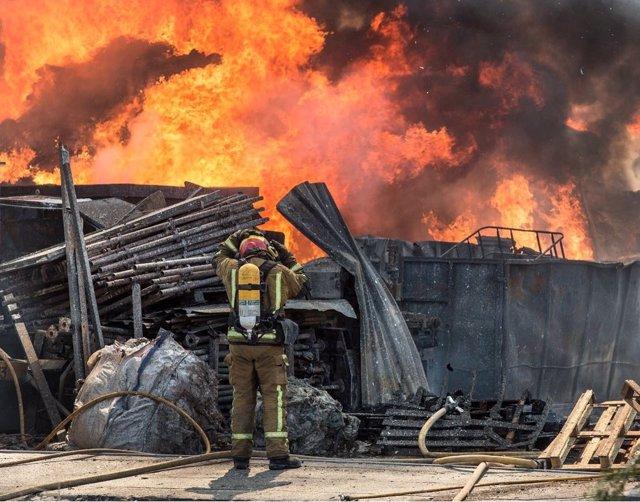 Un bombero trabaja en el incendio de la nave de reciclaje