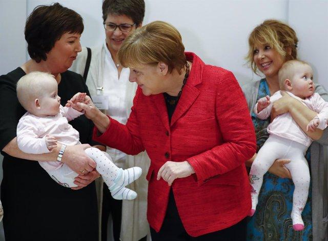 Foto de archivo de la canciller alemana, Angela Merkel, saludando a una bebé.