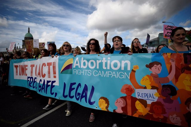 FILE PHOTO: Demonstrators hold posters as they march for more liberal Irish abor