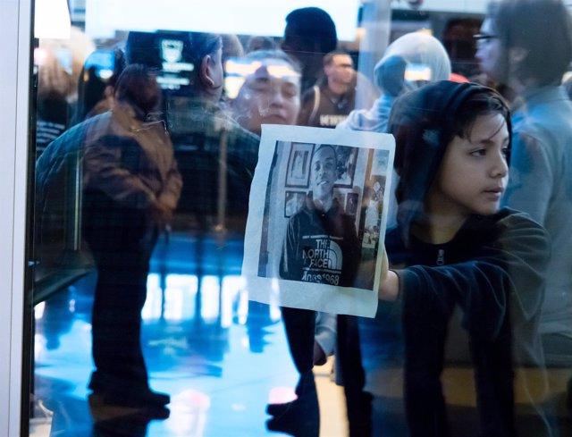 Un joven manifestante sostiene una foto de Stephon Clark