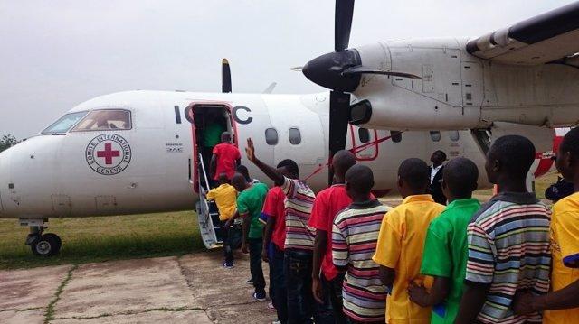 Niños soldados desmovilizados suben a un avión de CICR en RDC