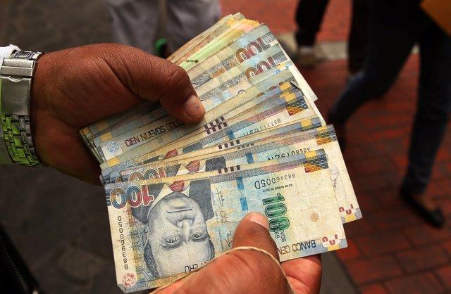 A money changer holds Peruvian Sol bills at a street in downtown Lima, Peru, Dec