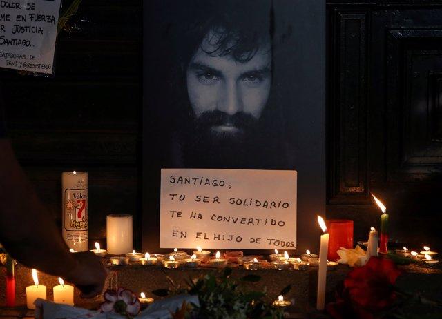 A man lights candles next to a portrait of Santiago Maldonado, a protester who w