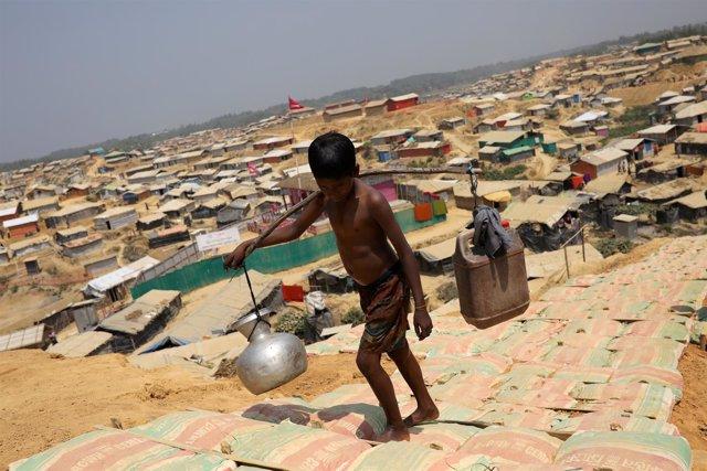 Un niño rohingya transporta agua en un campo para refugiados en Bangladesh