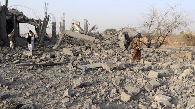 Personas caminan entre los restos de una casa destruida en Saada