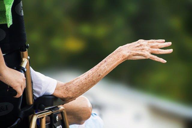 Mano de una persona anciana en silla de ruedas
