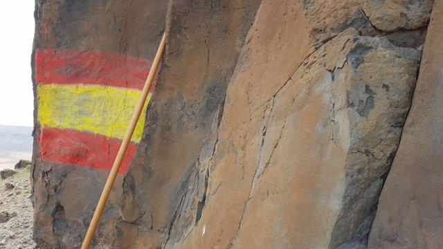 Pintada de una bandera de España sobre unos grabados pehispánicos