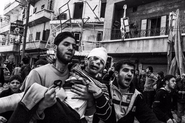 Un hombre carga a un niño herido tras un bombardeo
