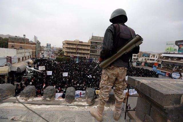 Combatiente huthi vigila una manifestación en Saná