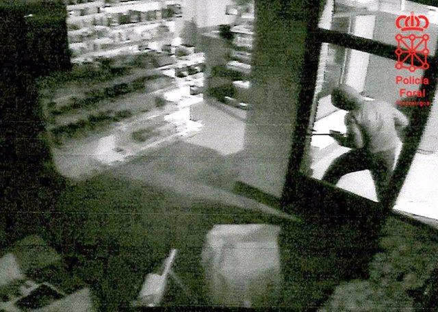 Uno de los ladrones intentando robar en una gasolinera