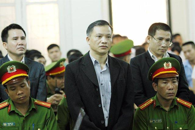Vietnamese dissident Nguyen Van Dai (C) stands at a court in Hanoi, Vietnam Apri