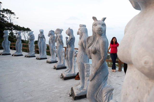 Una mujer posa junto a las polémicas estatuas en la ciudad de Hai Phong.