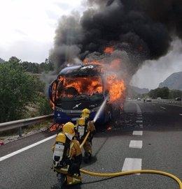 Dos bomberos atacan las llamas del autobús en Benissa