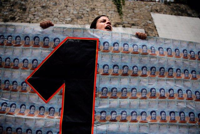 Manifestante con una pancarta con billetes de 2 bólivares