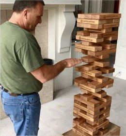 Un hombre jugando a la Jenga intentando sacar una pieza
