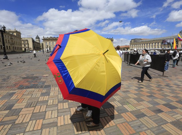 Voters walk while carrying an umbrella with the color of the Colombian flag afte