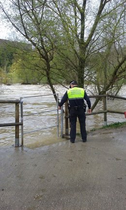 Un agente supervisa el cierre de las pasarelas peatonales por la crecida del río