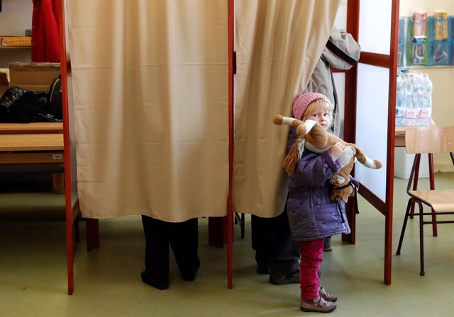 Una niña espera en un colegio electoral de Hungría.